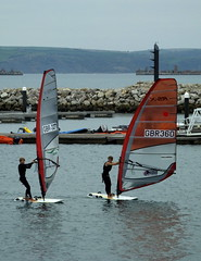 Elite junior wind-surfers coming ashore with very little wind... they flap the sails to make progress to the slipway... (Sue - happy sparrow) Tags: portlandharbour wpsa sailingacademy portland dorset windsurfing elitesailors sailors juniorsailors jurassiccoast