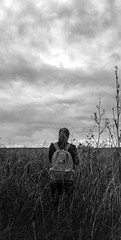Curious (npb94) Tags: curious girl possibilities bw blackwhite contrast clouds grass backpack