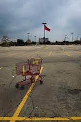 (295/366) Cart and Flag (CarusoPhoto) Tags: iphone 7 plus shopping cart mundane banal ordinary everyday john caruso carusophoto photo day project 365 366 dusk natural light parking lot lines flag abandoned empty