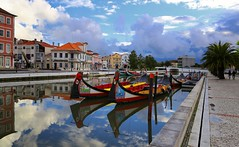 The sky cleared up after a day of rain in Aveiro (Bn) Tags: portugal aveiro moliceiros boat gondel traditionally charm magic hidden gem reflections water canals maritime colour fishermen paintwork azulejo fishing veice lagoon urban festival seaweed tourist holiday vacation pink yellow colors blue round city hopping ornate images man woman clouds weather after rain gondelas