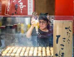 Takoyaki girl (Kostas Trovas) Tags: delicious 50mm portrait action tourism service kostasimages japanesefood cooking streetfood streetphotography octopus canon 6d snack drizzling tasty instagram kiosk girl cook candid travel flickr woman 500px   food yummy japan takoyaki