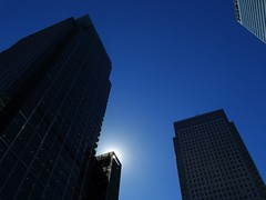 Looming (Deepgreen2009) Tags: blue sky urban sun london towers tall canarywharf offices