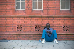 Chilling Out (Howie Mudge LRPS) Tags: man male person sit sitting wall pavement cardiff buidling bricks window headphones phone windows trainers relax relaxing bay caerdydd candid capital city street streetlife streetphotography urban urbanphotography sonyrx100mkiv sonydscrx100m4