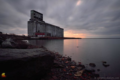 The Old Faithful (DTD_1805) (masinka) Tags: grain elevator cargill pool lake erie outer harbor buffalo ny newyork western upstate historical building structure industrial longexposure sunset clouds motion rocks beach gallagher dramatic light lakeshore shoreline icon hallmark concrete etbtsy