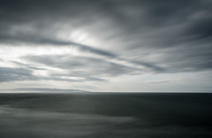 Seascape - Long Exposure, Almost Achromatic (byron bauer) Tags: byronbauer pacific ocean sea beach water sky clouds sun longexposure timeexposure currents wind blur movement ethereal horrizon hills mountains shoreline cloudy nebulous painterly grey stormy streak