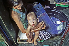 Happy Land... (carf) Tags: poverty woman baby children community child philippines poor mother forsakenpeople social manila shanty bathtub forsakenplaces washing survival slum filipinos aroma atrisk happyland childrenatrisk ulingan newsmokeymountain forasaken