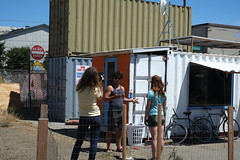the iteration process began with the first shipping container house, including iseman and may's tiny house (behind them) (nicolas.boullosa) Tags: california oakland entrepreneurship newurbanism containerhouse tinyhouses shippingcontainerhouse americansteelstudios leanurbanism smallprefab containerurbanism boxouse postapocalipticurbanism