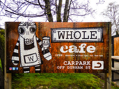 The Whole Cafe (Steve Taylor (Photography)) Tags: whole cafe smile teeth cross w arrow turn convict cup eyes art design sign bench black brown green white metal newzealand nz southisland canterbury christchurch cbd city grass tree iron rust corrosion rivet coffee takeaway
