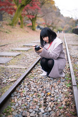 Young woman taking pictures on dead railroad track (Apricot Cafe) Tags: 20s asianethnicity japan japaneseethnicity kyoto minikyoto2016 sigma35mmf14dghsmart autumn autumnleaves beautyinnature camera change charming cheerful enjoying foliage freshness happiness hope japanesefallfoliage japanesemaple leaves mapleleaf nature oneperson onlywomen outdoors people railroadtrack refreshing selectivefocus takingpictures tranquility traveldestinations walking wishing woman youngadult