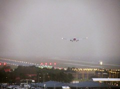 Wet arrival (Amateur-Hour Photography) Tags: sky rain clouds canon shower airport aircraft planes syd runway hotelview airliners sydneyairport yssy rwy16l runwayapproach