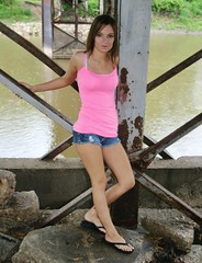 Under the Bridge (PhotoAmateur1) Tags: park pink blue portrait woman brown green feet water beautiful beauty smile face grass smiling shirt river bench hair skinny outside outdoors photography model eyes rocks toes photoshoot arms legs head top background gorgeous country young lips jeans flipflops denim shorts brunette lovely photosession slender daisydukes