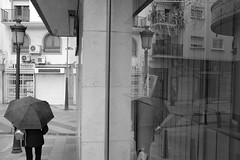 El paraguas B&N (Desde mi Fujifilm) (SerChaPer) Tags: fujifilmx100t monochrome monocromo blackandwhite blancoynegro paraguas umbrella lluvia rain escaparate showcase reflejo reflection farola streetlight steetphoto fotocallejera persona people ceuta
