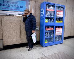Subway Station Conversation (Mondmann) Tags: subway subwaystation conversation phoneconversation cellphone smartphone emergencysupplies supplycabinet seoul korea southkorea rok republicofkorea asia eastasia korean man mondmann fujifilmxt10