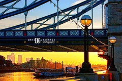 Sun Rising in the City (david gutierrez [ www.davidgutierrez.co.uk ]) Tags: city uk morning bridge light sun london water thames clouds towerbridge sunrise buildings river boats photography golden glow amanecer canarywharf towerhill eastlondon davidgutierrez so