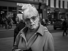 Something Vexes Thee (Leanne Boulton) Tags: people monochrome depthoffield urban street candid portrait portraiture streetphotography candidstreetphotography candidportrait streetportrait eyecontact candideyecontact streetlife old age elderly woman female face facial expression look emotion feeling eyes teeth skin wrinkles tone texture detail bokeh natural outdoor light shade shadow naturallight city scene human life living humanity society culture canon 7d 50mm black white blackwhite bw mono blackandwhite character glasgow scotland uk