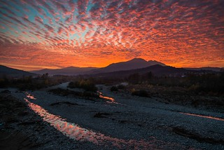 colorful sunset and reflection in Marecchia river