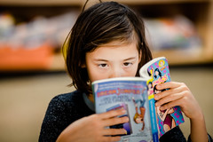 The reading girl (michaelinvan) Tags: reading comics book school canon 5d2 135mm f2 dof young kid eyes cool portrait portraiture woman face classroom indoor availablelight existinglight