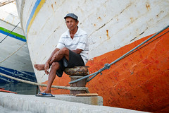 Has been sitting here a while - Sunda Kelapa Old Harbor, Jakarta, Indonesia (Maria_Globetrotter) Tags: 2016 fujifilm indonesia mariaglobetrotter dscf51492 portrait old man sitting rust boat ship indonesian jakarta relaxed cool colorful smile