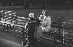Well Fed (L. A. Nolan) Tags: park city nyc newyorkcity trees blackandwhite bw food woman baby ny newyork film grass 35mm fence bench outside holga kid toddler gate day child stroller centralpark manhattan mother streetphotography 400 feed ilfordhp5plus400 parkbench ilford ilfordhp5plus holga135bc