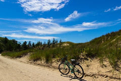 Lighthouse Road (kirsten.elise) Tags: road blue trees light summer green beautiful sunshine bike clouds forest canon sand day fuji bright path michigan dunes dry sunny pines bikeride ludington dunegrass westmichigan ludingtonstatepark canonphotography lighthouseroad scenicmichigan puremichigan canonrebelt3i