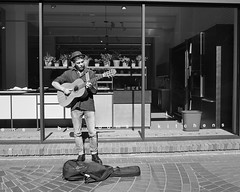 A One-Man Traveling Band. (vanessadoban) Tags: bcitbroadcast bcitbroadcastonlinejournalism photojournalism visualfundamentals vanessadoban vanessadobanbcitbroadcast portraiture blackandwhite travelingmusician guitarplayer streetperformer vancouverbusker vancouvermusicscene
