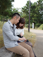 Young couple looking at digital tablet together (Apricot Cafe) Tags: portrait male smiling japan female asian japanese tokyo young lifestyle happiness casual relaxation youngcouple photosession minato 20s tokyo modelshooting odaiba digitaltablet modelreleaseready sigma35mmf14dghsm img67885 odaibamarinepark