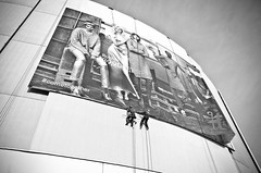 _DSC6595 (stimpsonjake) Tags: nikoncoolpixa 185mm streetphotography bucharest romania city candid blackandwhite bw monochrome billboard sign mall hm men workers work highcontrast