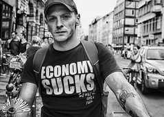 Economy (Blinkofanaye) Tags: street portrait people bw berlin germany candid under tshirt stranger sucks slogan financial economy crisis