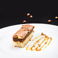 Chocolate Layer Cake with caramel, nuts and chocolate on white plate, (Natalia Zakharova) Tags: food brown white up cake studio pie table dessert yummy beige shot bright sweet chocolate vibrant background napkin traditional cream mint tasty plate fresh creme gourmet delicious biscuit caramel slice bakery single tiramisu layers treat appetizer nut piece cocoa celebrate decorate bake culinary isolated indulgence mousse mascarpone fattening layered