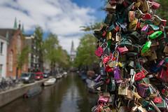 Locksmiths love lovelocks (Janet Marshall LRPS) Tags: lovelocks padlocks love bridge canal amsterdam church