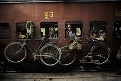 038-9%20bicycle%20train - Copia (hollysingerlow) Tags: 1983 india daccatopeshawar april 041983 horizontal portrait outdoors outside exterior adult adults man men woman women young old passenger passengers ride riding train trains railroad travel transportation bike bikes bicycle bicycles window windows red brown yellow 0024604 india11443 iconicphotographs imperialway pakistan10070 untold thestoriesbehindthephotographs phaidon