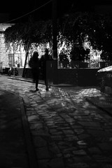 Walk in sync (Elios.k) Tags: street camera travel light shadow summer vacation two people blackandwhite bw woman man motion travelling silhouette vertical night canon dark walking outdoors photography bay movement couple village pavement walk vine august cobblestone greece together narrow pelion paved handinhand magnisia pagasitic lafkos 5dmkii
