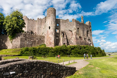 Impressive Welsh castle at Laugharne (Keith in Exeter) Tags: welsh impressive laugharne castle carmarthenshire wales fort fortress fortification battlement wall tower architecture ruins bridge tree bush grass path outdoor landscape people
