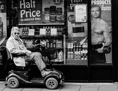 Fit for purpose (pootlepod) Tags: street blackandwhite window monochrome muscles wheel electric shop lady photography chair scooter health elderly vitamins shopper stphotographia