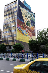 An anti-Israel and anti-USA mural in the city of Teheran, Iran, portraying an arm waving a flag and imam Ruhollah Musavi Khomeini. (Jeppe Schilder Photography) Tags: street city urban usa art cars schilder wall museum canon painting photography graffiti israel support mural war asia paint gun fotografie traffic unitedstates iran flag taxi islam unitedstatesofamerica protest middleeast streetphotography murals persia bookstore embassy demonstration conflict leader shiraz statueofliberty muslims revolver martyrs 1979 enemy teheran antiamerica jeppe imam honour diplomacy antiusa khomeini honouring usaembassy imamkhomeini downwithusa alikhamenei diplomaticmission ruhollahmusavikhomeini iraqiranwar imamkhamenei jeppeschilder seizureoftheembassy proteststudents wwwjeppeschildercom
