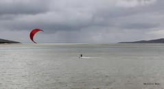 Watersports in Harris with a blast of red (mootzie) Tags: outerhebrides skygrey windsurfing yellowblueseaaqua kitered watersports harris scotland luskentyre wetsuit surfer sea sand hills scotlandouter hebrides red