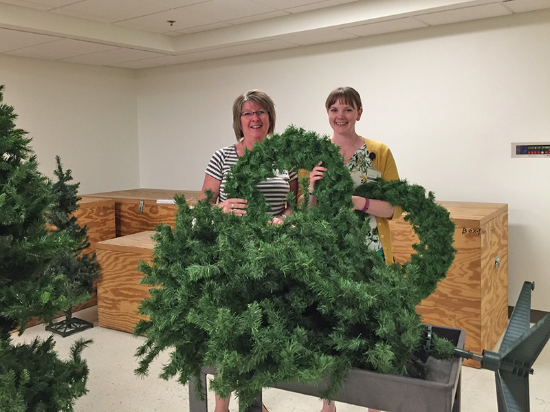 Staff members pick up wreaths and trees