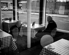 A Lonely Man In A Chip Shop - South Shields (Richard James Palmer) Tags: mamiya7ii mamiya 7ii 80mm ilford hp5 ilfordmicrophen microphen ishootfilm shoot film iso 400 iso400 ilfordhp5 f4 newcastle northeast north east street photography streetphotography portrait black white rangefinder medium format 120 filmisnotdead analogue documentary epsonperfectionv700 epson v700 1125 newcastleupontyne upon tyne tyneandwear northern uk england urban melancholy art fineart new overcast isolated walkabout 2016 gritty gloomy abstract trapped blackandwhite monochrome south shields