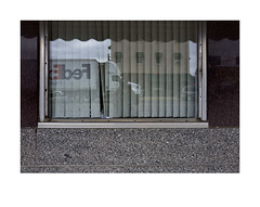Window of a closed, small town bank (Richard C. Johnson: AKA fishwrapcomix) Tags: leicaq summilux28mm f17 paxamericanus endofempire digital duluth aitkin minnesota midwest color wetzlar reddot window reflections selfportrait decline economicdownturn thegreatrecession sunsetsinthewest civisromanussum street granite outdoor he