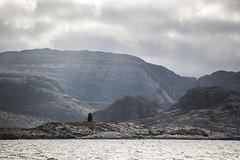 Surrounding (Gabriel Berg) Tags: mountains water norway haze rocks layers sunbeam bessaker