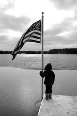 Laying Claim (sethswife) Tags: winter blackandwhite lake cold child pentax michigan americanflag possession basslake ownership k7