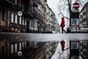 Little Red (ewitsoe) Tags: faerietale urban city littleredridinghood ewitsoe reflection cityscape nikon d80 35mm puddle red cloak cape woman stop walking poznan poland polska europe