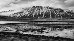 Isafjordur drive-by view (lunaryuna) Tags: iceland northiceland isafjordur fjord mountainrange landscape seascape water shoreline driveby journey ontheroad snowcappedmountain reflections town blackwhite bw monochrome lunaryuna