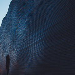 the wall is made of lava (itawtitaw) Tags: wood morning blue light orange sun abstract color reflection building lines architecture facade contrast corner sunrise munich square glow edge gradient curve tu audimax minimalist divided fassade woodenplanks canoneos5dii canon2470mm28ii merkleholzbau