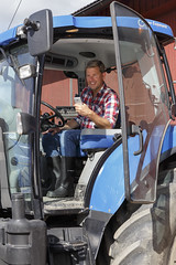 Farmer using DeLaval InService Remote in tractor (DeLaval press centre) Tags: tractor man male smartphone mobilephone farmer delaval remoteconnect