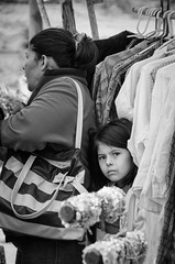 Market Girl (mightymuffinful) Tags: mexico market portrait girl blackandwhite face travel eyes hiding soulful pike sweet streetphotography clothing shopping people