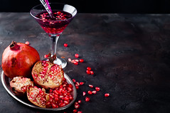 Pomegranate, cut into sections on a metal dish in the background of the shot glasses (lyule4ik) Tags: