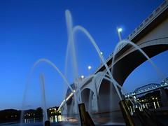 Tennessee Aquarium Fountains + Riverfront Skyline (Roland 22) Tags: blue orange white reflection lights evening twilight flickr glow dusk tennessee jets spray northshore walnutstreetbridge shining tennesseeriver waterfountains chattanoogatn tennesseeaquarium marketstreetbridge