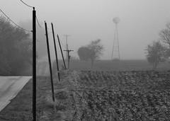 in sync.... (BillsExplorations) Tags: telegraphtuesday powerlines windmill windmillwednesday fog mist road countryroad rural field winter blackandwhite monochrome