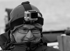 Hero 3 (Neil. Moralee) Tags: street camera old portrait blackandwhite bw white man black cold monochrome face hat norway mono glasses nikon photographer action head candid band neil svalbard arctic mature hero wooly 18200 straps longyearbyen polycarbonate gopro d7100 moralee neilmoralee svalbardnorwaylongyearbyenneilmoralee
